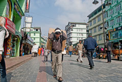 M G Marg, Gangtok. Porters are carrying heavy good and household furniture on their back through Mahatma Gandhi Marg in Gangtok, Sikkim, India. Vehicles are Stock Images