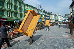 M G Marg, Gangtok. Porters are carrying heavy good and household furniture on their back through Mahatma Gandhi Marg in Gangtok, Sikkim, India. Vehicles are Royalty Free Stock Photo