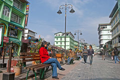 M G Marg, Gangtok. Tourist and local people are sitting on the roadside bench enjoying a sunny morning at Mahatma Gandhi Marg, the main business and tourism Stock Image