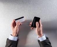 M-komrets med affärsmannen räcker den hållande kreditkorten och telefonen Royaltyfria Bilder
