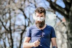 M?le brutal barbu fumant la cigarette ?lectronique Hippie m?r avec la barbe E-cigarette de tabagisme d'homme prise d'homme de hip images libres de droits
