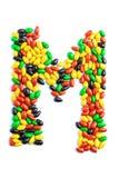M Letter do alfabeto feito dos doces isolados no fundo branco imagem de stock