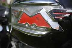 M letter with wings from a Matchless motocycle. Red and chrome logo, greys, screw head and sunny, vintage old 3d letter on petrol tank Stock Photography