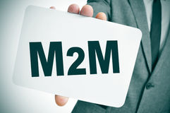 M2M, for the machine to machine technologies. A businessman showing a signboard with the text M2M, for the machine to machine technologies, written in it Royalty Free Stock Photography