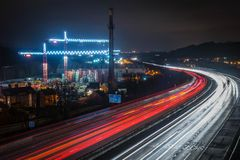 Motorway And Industry At Night. The M1 motorway in England passing industrial cranes at night. Cars can be seen speeding by royalty free stock photos