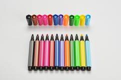 M?ng- kul?ra pennor f?r kl?dd med filt spets p? vit bakgrund royaltyfri bild
