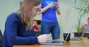 m?nga active mobil telefon genom att anv?nda kvinnan Dekoratörs kollegor som tillsammans arbetar på en innovativ produktdesign i  arkivfilmer