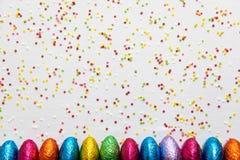 M?nga arrangera i rak linje kul?ra chokladeaster ?gg p? vit bakgrund och f?rgrika konfettier royaltyfri fotografi