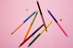 M?nga blyertspennor p? en rosa bakgrund royaltyfria bilder