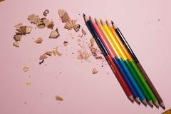 M?nga blyertspennor p? en rosa bakgrund royaltyfri fotografi