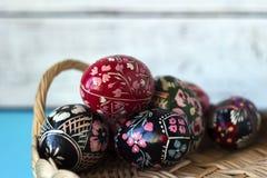 M?nga dekorerade p?sk?gg ligger i en korg, en whte och en bl? bakgrund Ukrainska p?sk?gg med prydnader och modeller royaltyfri fotografi
