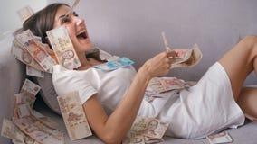 M?nga sedlar flyger i luftfasta utgiften i ultrarapid En flicka ligger och mycket pengarnedg?ngar p? henne den lyckliga kvinnan j arkivfoto