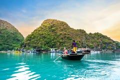M?nner, die Sampan mit dem touristischen Kayak fahren in Halong-Bucht rudern lizenzfreies stockfoto
