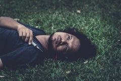 M?nner tot auf dem Gras und der Blutung vom Mund, nachdem zu viel eingespritzt worden ist Konzept der Drogensucht und der ?berdos stockbild