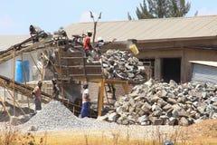 M?nnliche Arbeitskr?fte arbeiten in den harten Bedingungen an einem afrikanischen Steinbruch, der manuelle Arbeit erledigt lizenzfreie stockfotografie