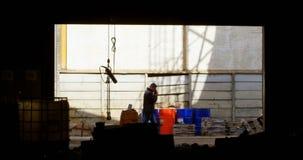 M?nnliche Arbeitskraft, die am Handy in der Werkstatt 4k spricht stock footage