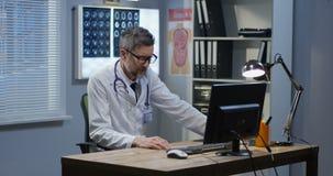 M?nnlicher Doktor, der beim Videoanruf spricht stock footage