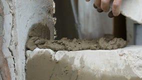 M?nnlicher Erbauer, der wei?en Ziegelstein auf Zement legt und Wand steht H?nde des Mannes die Mauerziegel legend nah herauf Ansi stock footage
