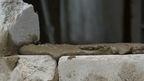 M?nnlicher Erbauer, der wei?en Ziegelstein auf Zement legt und Wand steht H?nde des Mannes die Mauerziegel legend nah herauf Ansi stock video footage