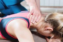M?nnlicher manueller viszeraler Therapeutmasseur behandelt einen jungen weiblichen Patienten Redigieren des Halses und der Wirbel stockfotografie