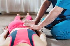 M?nnlicher manueller viszeraler Therapeutmasseur behandelt einen jungen weiblichen Patienten Redigieren des Schenkels lizenzfreie stockfotos