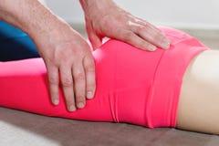 M?nnlicher manueller viszeraler Therapeutmasseur behandelt einen jungen weiblichen Patienten Redigieren des Schenkels lizenzfreie stockfotografie