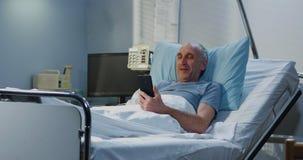 M?nnlicher Patient, der Videoanruf im Krankenhauszimmer verwendet stockbild