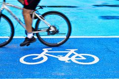 M?nnlicher Radfahrer reitet ein Fahrrad auf den Weg des Fahrradzeichens stockfotografie