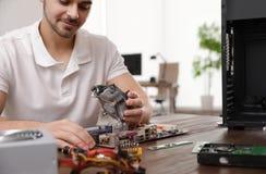M?nnlicher Techniker, der bei Tisch Computer repariert stockfoto