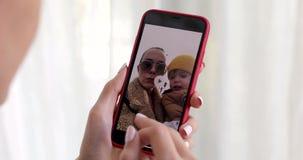 M?o da mulher com imagem da crian?a da exibi??o do smartphone video estoque