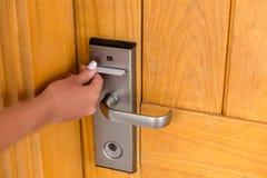 M?o da mulher com o keycard no fechamento eletr?nico cart?o chave da posse f?mea da m?o e porta de fechamento eletr?nica aberta foto de stock