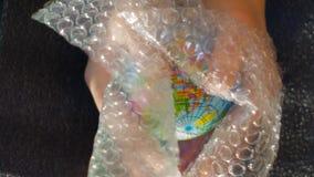 A m?o de um adolescente guarda um globo pequeno, acima ele parece uma folha do inv?lucro com bolhas de ar, metragem ideal represe imagens de stock royalty free