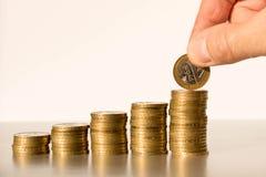 A m?o de um homem que p?e moedas em umas pilhas Conceito do neg?cio e crescimento do capital imagem de stock royalty free