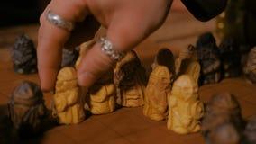 M?o do homem que coloca figuras para o jogo de mesa popular medieval da estrat?gia - tafl video estoque
