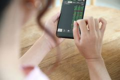 M?o f?mea com o estoque da troca do smartphone em linha na cafetaria, conceito do neg?cio fotos de stock royalty free