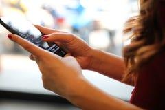 M?o f?mea com o estoque da troca do smartphone em linha na cafetaria, conceito do neg?cio foto de stock royalty free