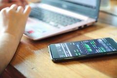 M?o f?mea com o estoque da troca do smartphone em linha na cafetaria, conceito do neg?cio fotos de stock