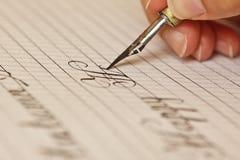 A m?o f?mea escreve com a pena manchado de tinta em uma folha do Livro Branco com listras artigos de papelaria no fim da mesa aci foto de stock royalty free