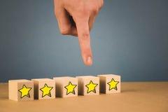 a m?o faz uma escolha e escolhe uma das estrelas, em um fundo azul fotos de stock royalty free
