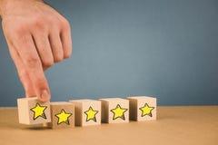 a m?o faz uma escolha e escolhe uma das estrelas, em um fundo azul fotos de stock