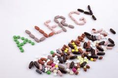 M?o que escreve o conceito dos cuidados m?dicos escrito com palavra ALERGIA da c?psula das drogas dos comprimidos no fundo isolad imagens de stock