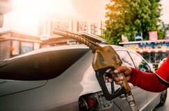 M?o que guarda o bocal de g?s no posto de gasolina para o reabastecimento do carro imagens de stock