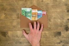 A m?o toma um envelope com dinheiro fotos de stock royalty free