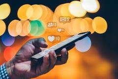 M?o usando o telefone esperto com conceito social dos meios fotografia de stock