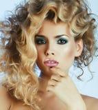 M?oda ?adna blond kobieta z wzrost fryzury k?dzierzawy pozowa? elegancki w b??kit sukni zbli?eniu zdjęcie stock