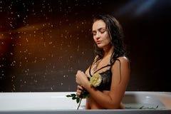 M?oda ?adna brunetki kobieta w sk?paniu z wod? i bryzga i opuszcza w ciemnym pokoju zdjęcia royalty free