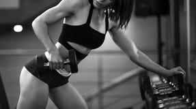 M?oda ?adna szczup?a kobieta w sportswear chwyta dumbbells w gym wn?trzu zdjęcia royalty free