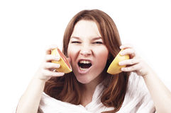 Młoda agresywna dziewczyna z grapefruitowy odosobnionym na bielu Zdjęcia Stock