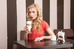 Młoda atrakcyjna dziewczyna pije cappuccino Zdjęcie Stock