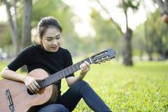 M?oda atrakcyjna kobieta bawi? si? gitar? akustyczn? zdjęcie royalty free